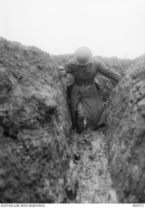 Description: Informal portrait of Captain C E W Bean, Official War Correspondent, knee deep in mud in Gird trench, near Gueudecourt in France, during the winter of 1916-1917